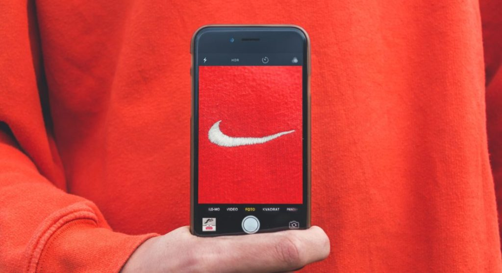 a person holding the phone with an image of nike brand